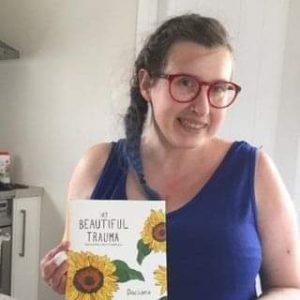 Georgiana holding her book, My Beautiful Trauma